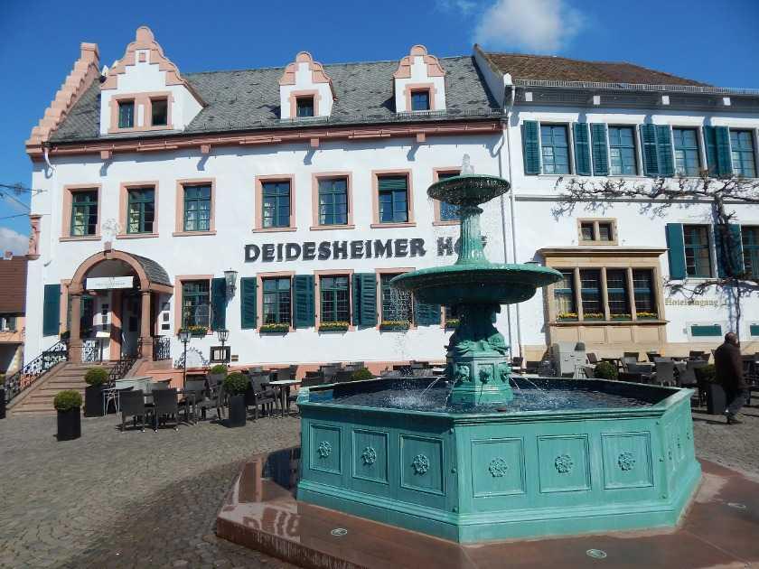 Der Deidesheimer Hof mit einem Brunnen davor am Marktplatz