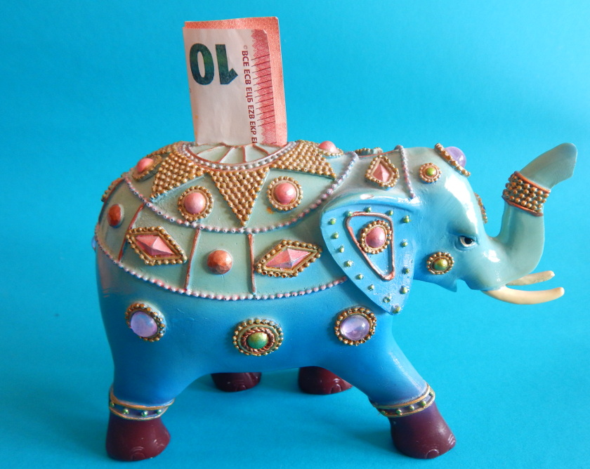 Geld sparen Urlaub. Spardose in Form eines Elefanten mit Geldschein