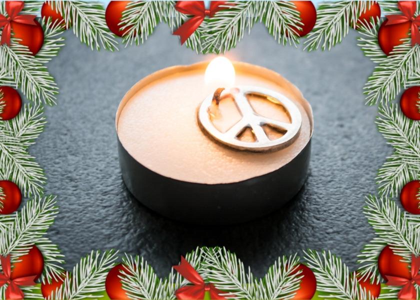 Eine brennende Kerze mit Peacesymbol und Tannenzweigenrand als Symbol für den Frieden.