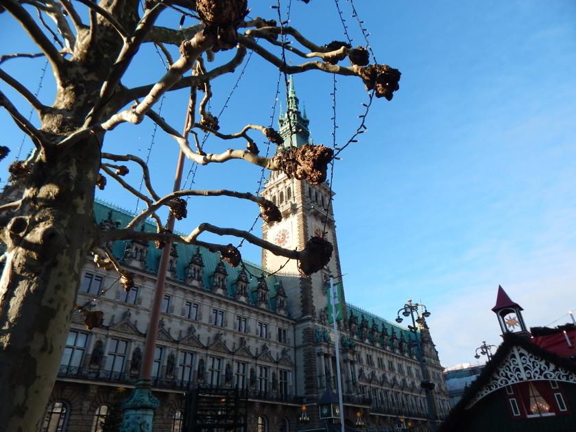 Weinachten in Hamburg, das Rathaus mit dem Weihnachtsmarkt im Sonnenschein.
